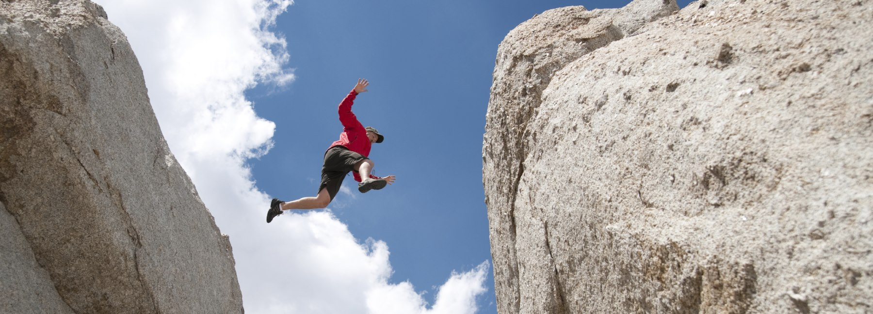 Man-jumping-from-one-giant-rock-to-another